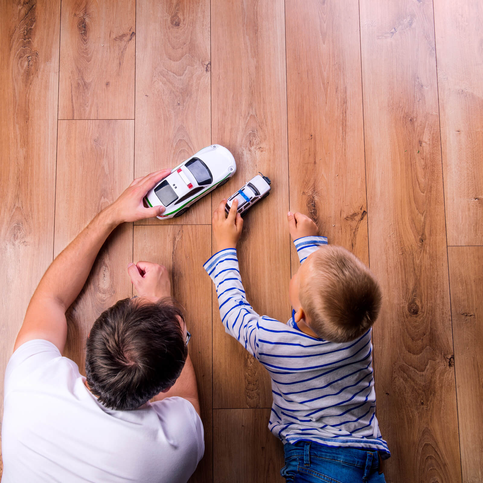 Dad child playing on Hardwood | Flooring By Design