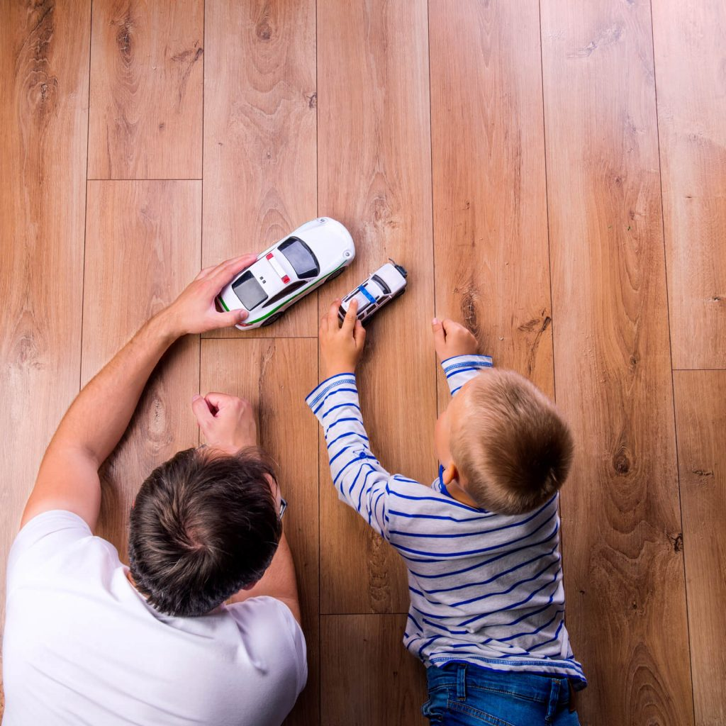 Father with kid playing with toycar | Flooring By Design